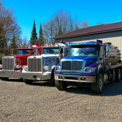 three black river transport trucks